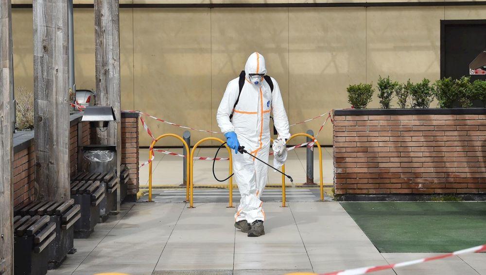 Un hombre desinfectando en Italia