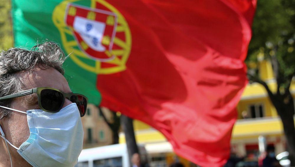 Un ciudadano pasa por delante de una bandera de Portugal
