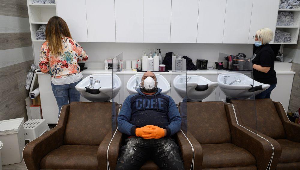 Un obrero hace una demostración durante la instalación de mamparas de separación entre las pilas para lavar cabezas en una peluquería de Alcalá de Henares, Madrid