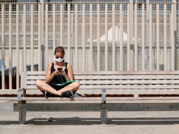 Una mujer con mascarilla, sentada en un banco de Barcelona