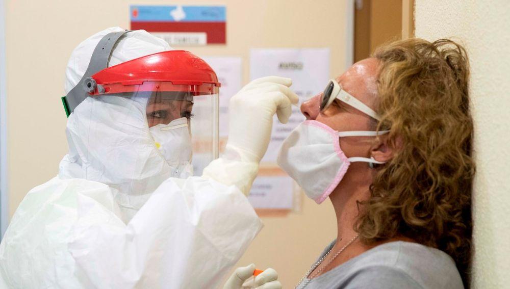 Una enfermera del 061 hace una prueba PCR a una mujer