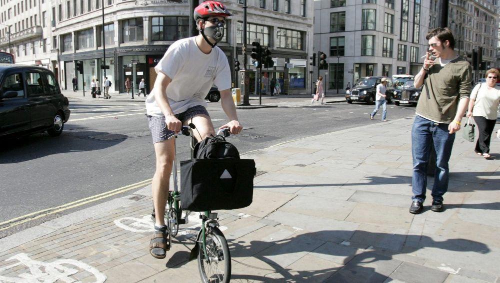 Un londinense se dirige a trabajar en bicicleta con mascarilla en la cara en Londres, Reino Unido.