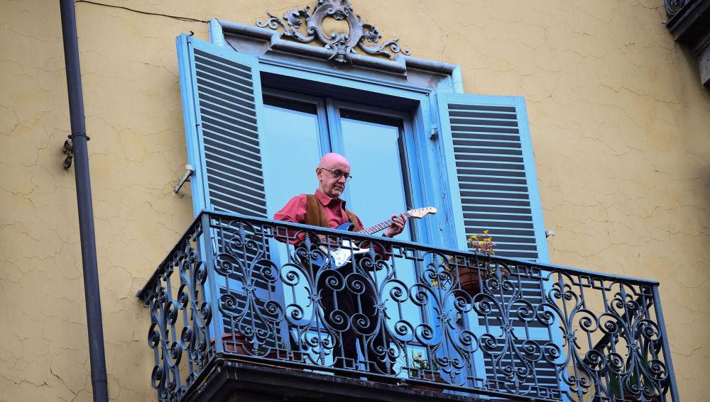 Un hombre toca la guitarra en su balcón, en una ciudad italiana
