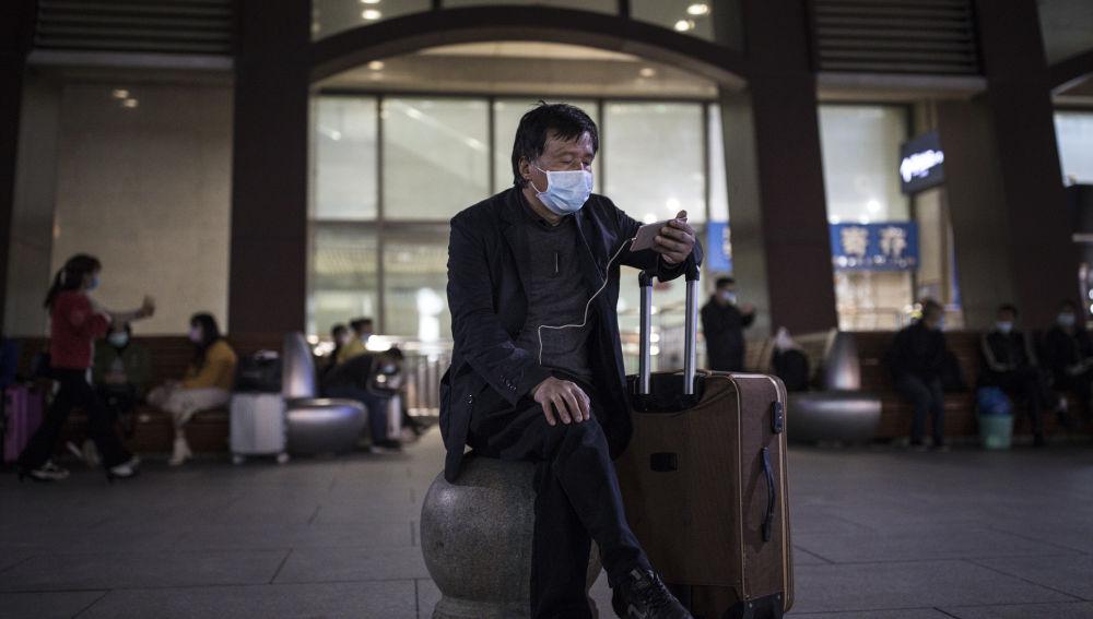 Un ciudadano en Wuhan mira su teléfono móvil