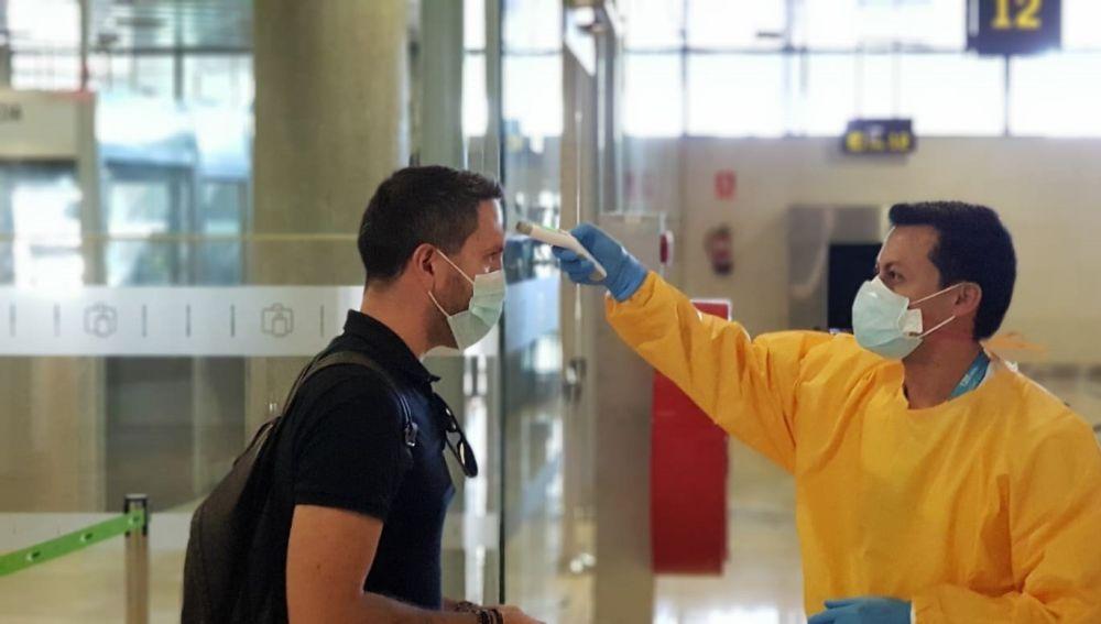 Toma de temperatura a un viajero en un aeropuerto.