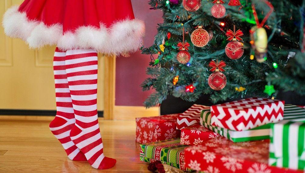 Una niña coloca el árbol de Navidad lleno de regalos