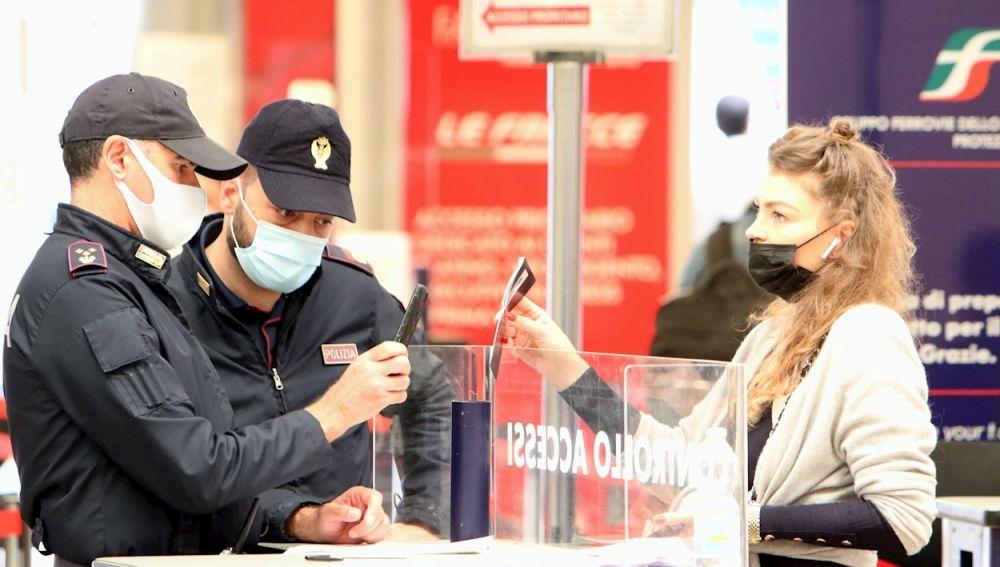 Agentes de las fuerzas del orden realizan controles a los pasajeros en la estación central de ferrocarril de Milán, Italia, el 2 de abril de 2021