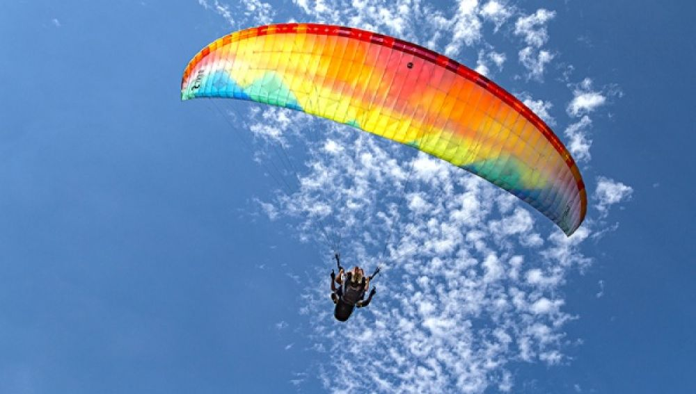 Un usuario disfrutando de las vistas de Menorca mientras vuela con el parapente.